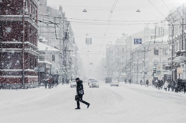 車と通行人、雪が降る雪に覆われた美しい忙しい街。悪い冬の条件の間に麻痺した都市 Premium写真