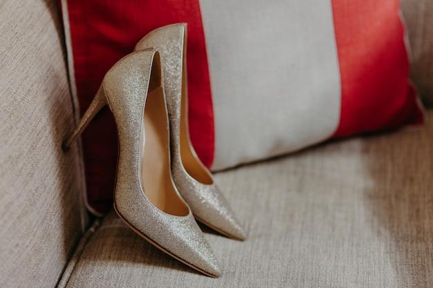 ソファの上のエレガントなハイヒールの女性の靴 Premium写真