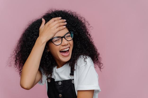幸せな満足のアフリカ系アメリカ人女性は額に触れて、活気があり、感情に訴える Premium写真