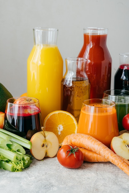 ガラス瓶、さまざまな食材、白い背景で新鮮な果物や野菜ジュースの垂直ショット。 Premium写真