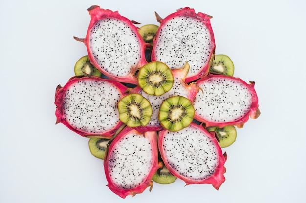 スライスしたグリーンキーウィとドラゴンフルーツが花の形で形成されました。 Premium写真