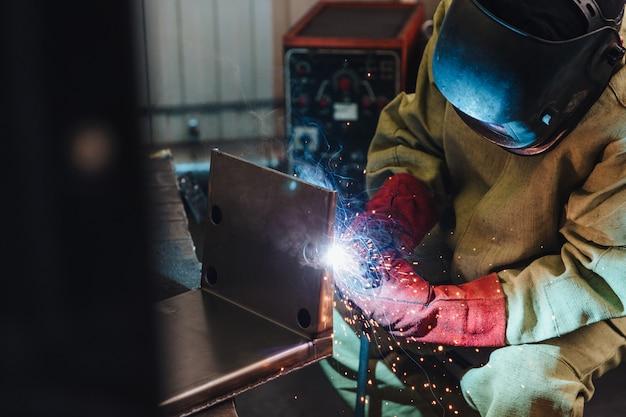 Концепция сварки. промышленный рабочий или сварщик носит защитную маску и перчатки, возводит техническую сталь на заводе Premium Фотографии