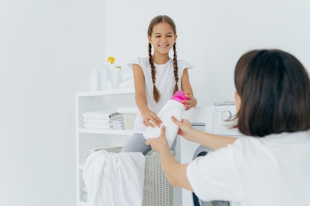 幸せな子ヘルパーと母親は、ランドリールームで楽しい時を過します、一緒に洗濯をします。国内作業コンセプト Premium写真