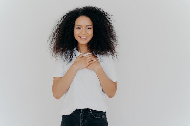 アフロの髪の陽気な女性は、胸に手を保ちます Premium写真