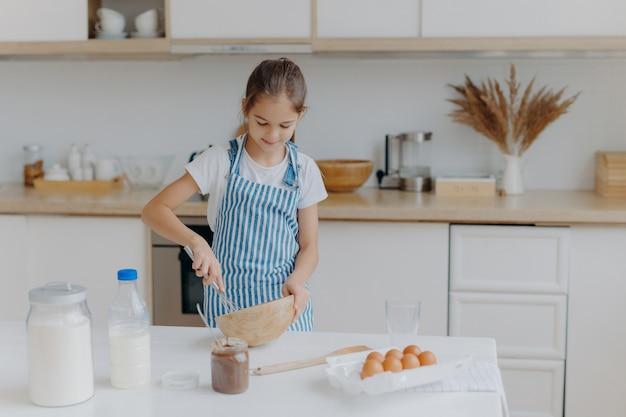 かわいい小さな女の子は縞模様のエプロンを着て、ボウルに材料を泡立て、生地を準備し、料理を教えます Premium写真