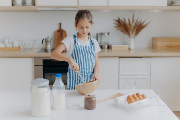 Маленькая милая девушка в фартуке, смешивает ингредиенты, взбивает венчиком, использует яйца, молоко, муку, пробует новый рецепт, выступает против кухни Premium Фотографии