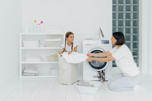 小さな子供は洗濯でママを助け、ランドリーでバスケットに座っています Premium写真