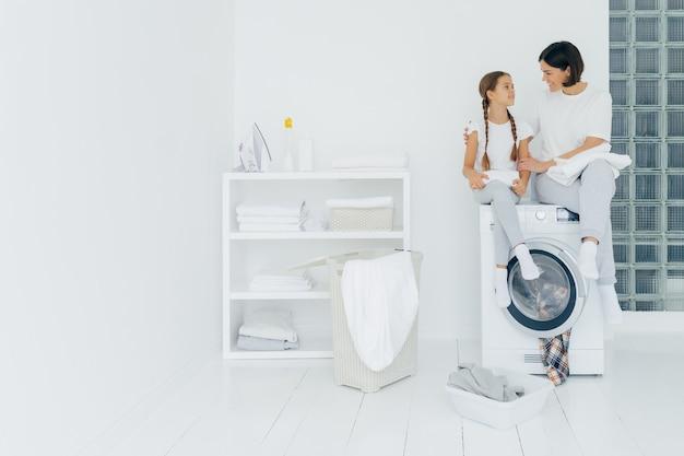 幸せな思いやりのある女性は彼女の小さな娘を包含し、洗濯機に座る Premium写真