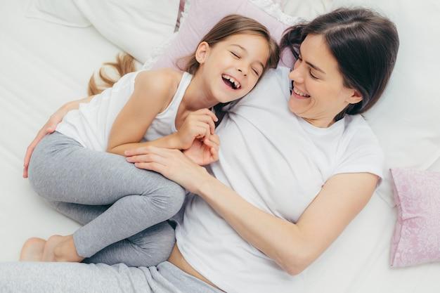 Прелестный ребенок и ее мама веселятся вместе в постели, щекочут друг друга, радостно улыбаются, играют после хорошего сна Premium Фотографии
