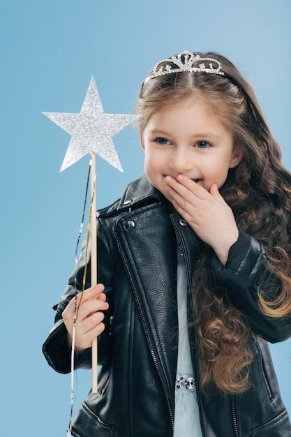 嬉しそうに見える小さな子供は、手のひらで口を覆い、積極的に笑い、王冠と黒い革のジャケットを着て喜んでいます Premium写真