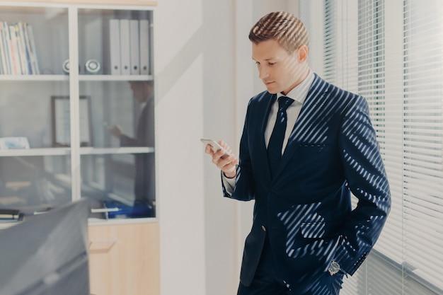 Красивый мужской предприниматель, читает текстовые сообщения Premium Фотографии