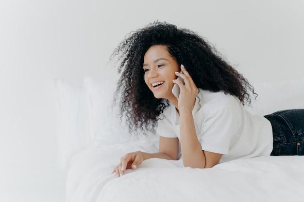 Очаровательная молодая женщина с хрустящими волосами, разговаривает с парнем через смартфон, утром отдыхает в постели Premium Фотографии