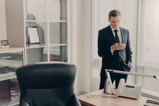 Менеджер по корпоративной одежде просматривает веб-страницы и чаты онлайн со смартфоном Premium Фотографии