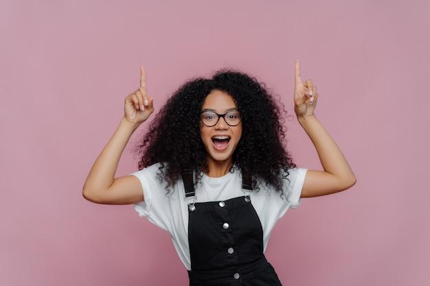 幸せなアフロアメリカンの女性は、両方の人差し指を上に指します Premium写真