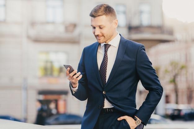 幸せなビジネスマンは、フォーマルなスーツと腕時計を着用し、スマートフォンを使用してポケットに手をつないでください。 Premium写真