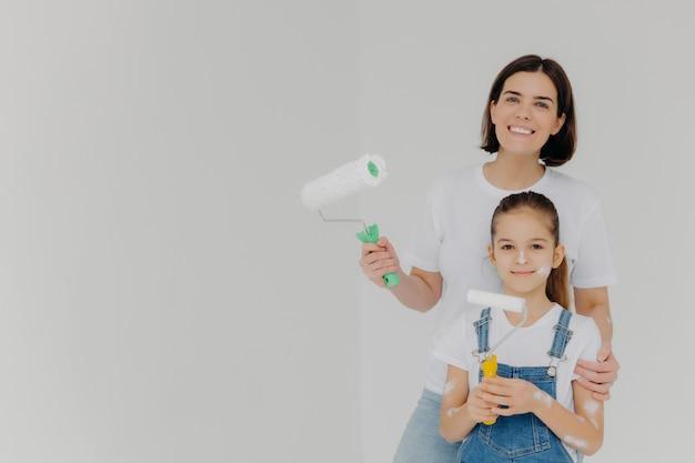 Улыбающаяся заботливая мама обнимает дочь, стоит с малярными валиками Premium Фотографии