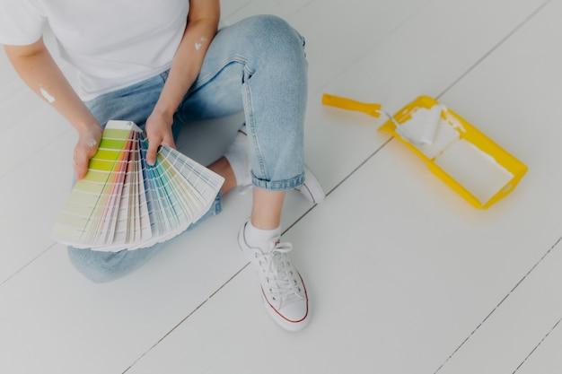 ジーンズの顔のない女性は、色のサンプルを保持し、改修壁に最適なトーンを選択します Premium写真