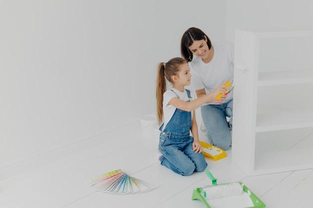 小さな女の子がローラーでペイントする方法を学ぶ Premium写真