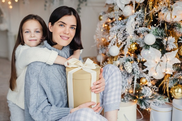 ありがたい小さな女性の子供は、プレゼントをくれた母親を抱きしめ、一緒に素晴らしい忘れられない時間を過ごし、クリスマスを祝います。ブルネットの女性と娘はモミの木の下でプレゼントを探す Premium写真