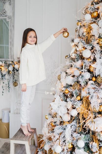 女児の縦向きの肖像画は、新年の木の近くに立ち、新年ボールを飾り、モミの木を飾り、幸せな表情を持ち、奇跡を期待しています。家族、クリスマス、休日、子供 Premium写真