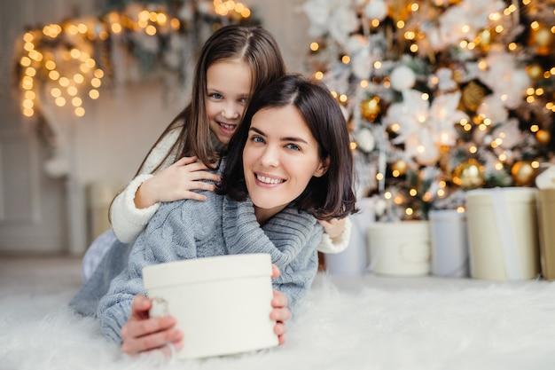 このプレゼントはあなたのためです!幸せな小さな子供は包まれたプレゼントを保持する彼女の愛情深い母親を受け入れます Premium写真