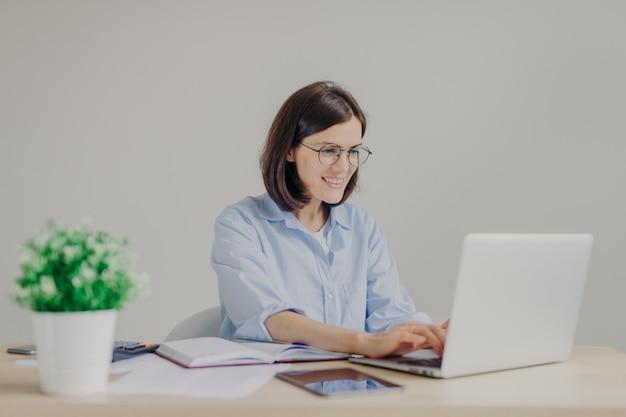 カジュアルなシャツと丸い大きな眼鏡で幸せな若い女性起業家は、ラップトップコンピューター上の情報を分析します Premium写真