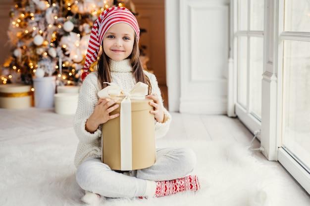 幸せな小さな子供が白いニットのセーターを着て、新年のツリーに対して居心地の良い部屋に贈り物を保持し、両親からクリスマスプレゼントを受け取って喜んで、快適さを感じています。幼年期、休日の概念 Premium写真