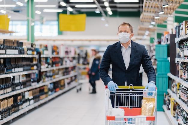 成人男性の写真は、使い捨てのフェイスマスクを着用し、買い物をし、保護について考え、コロナウイルス肺炎の発生時の対策を防ぎ、デパートでカートを使ってポーズをとります。流行時間 Premium写真