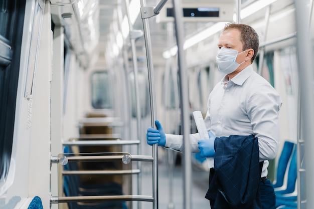 Концепция гигиены и безопасности вирусов. серьезный мужчина, одетый в элегантный наряд, одноразовую маску и резиновые перчатки, трогает за поручень в подземном вагоне, добирается до офиса во время карантина Premium Фотографии