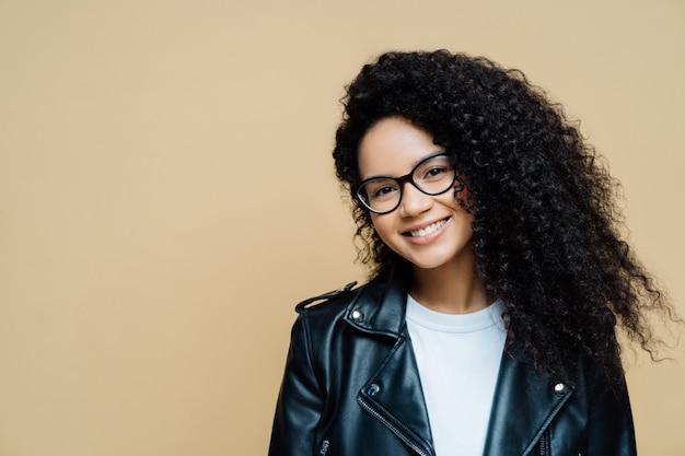 自然な巻き毛、楽しい笑顔で幸せな健康な女性 Premium写真
