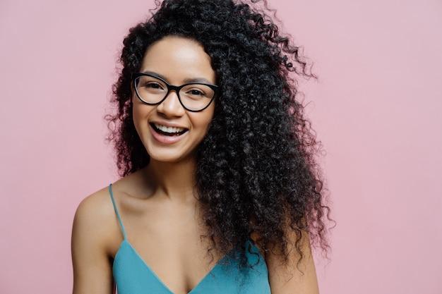 幸せなアフリカ系アメリカ人女性は喜びから笑う、健康な黒い肌、巻き毛、パステル色のバラ色の背景に分離 Premium写真