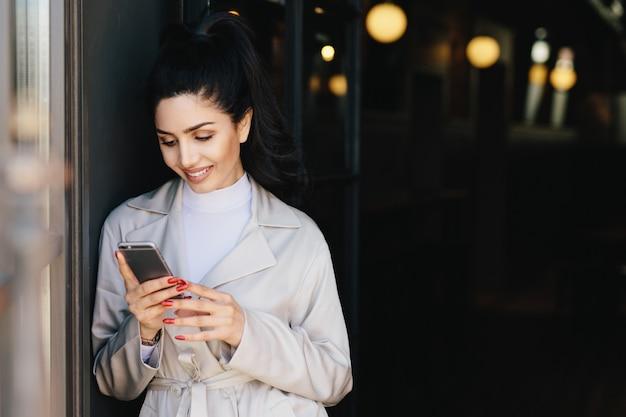 白いエレガントなコートに身を包んだポニーテールで結ばれた黒髪のファッショナブルな美しい女性 Premium写真