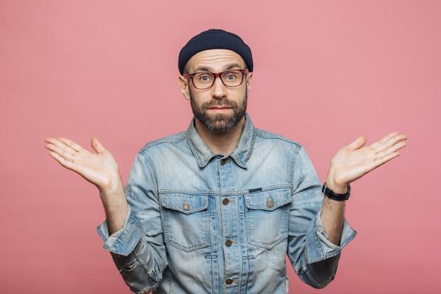 Фотография привлекательного бородатого мужчины носит модную одежду, пожимает плечами в недоумении Premium Фотографии