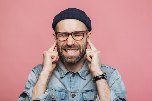 不快な音が聞こえ、目を閉じたまま、イライラしたひげを生やした男性が耳を塞ぐ Premium写真