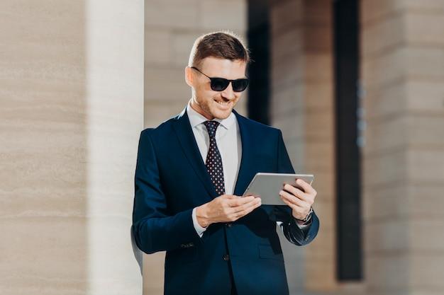 Привлекательный молодой человек читает важную информацию на планшетном компьютере Premium Фотографии
