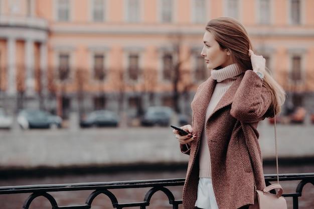 若い女性は思慮深い表情で脇に見える、現代の携帯電話を保持し、電話を待つ Premium写真