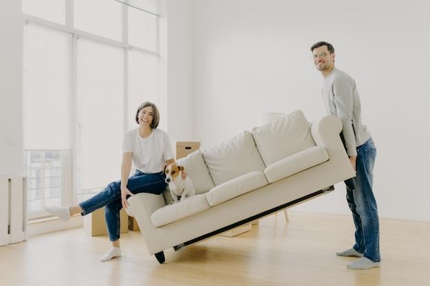 Муж и жена несут диван, обставляют гостиную после ремонта, с удовольствием покупают квартиру Premium Фотографии