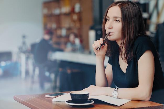 若い女子学生がレポートのメモを書き留め、コーヒーショップで働いて、カプチーノを飲む Premium写真