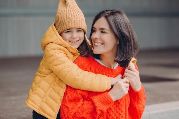 満足している魅力的な若い母親の写真は娘に積極的に見えます Premium写真