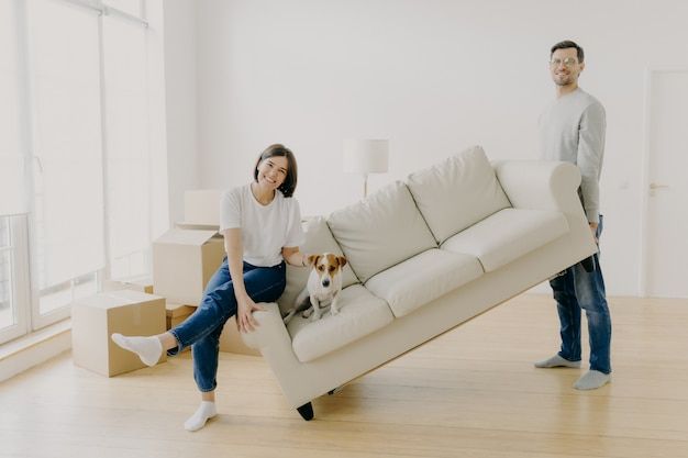 Счастливая пара переносит мебель в свой новый современный дом, носит диван с домашним животным, позирует в просторной комнате Premium Фотографии
