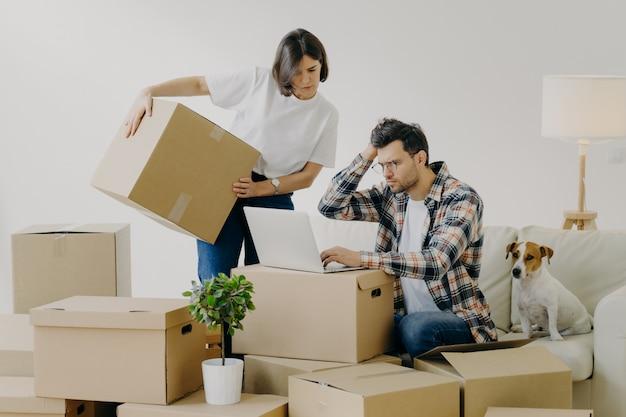 Движущаяся концепция. разочарованный молодой человек использует современный портативный компьютер для поиска необходимой информации в интернете, женщина заменяет большие картонные коробки на личные вещи. новый дом и концепция жизни Premium Фотографии