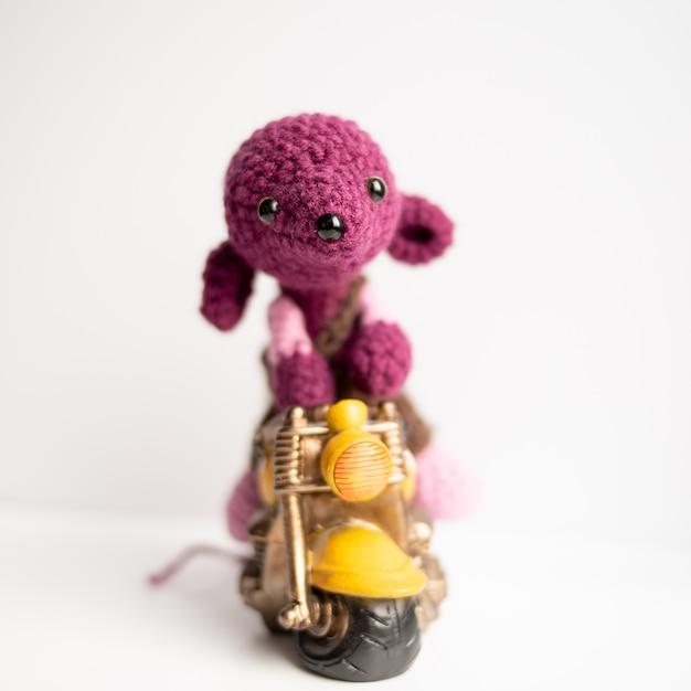 Вязаная игрушка ручной работы. крыса, связанная крючком с желтым мотоциклом Premium Фотографии