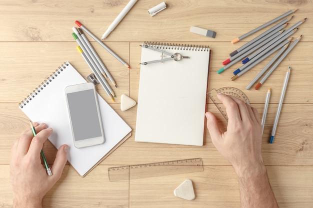 デザイナーは木製のテーブルの上のノートにスケッチを描きます。文房具。上からの眺め。 Premium写真