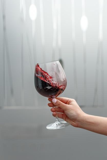 女性の手に赤ワインのグラス Premium写真
