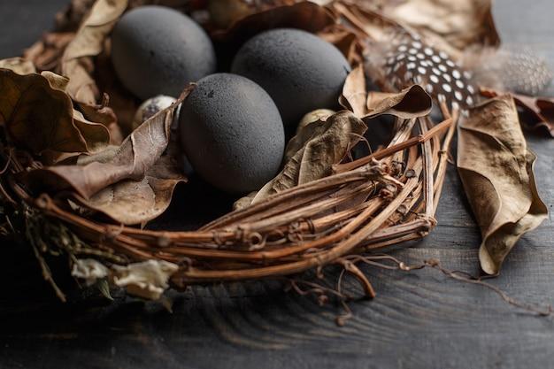 Черные яйца в гнезде сухих ветвей на черной доске. пасхальный стиль. Premium Фотографии