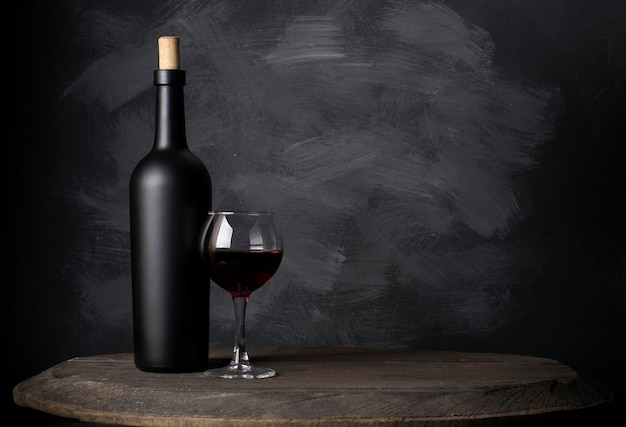 Бутылка красного вина на дереве Premium Фотографии