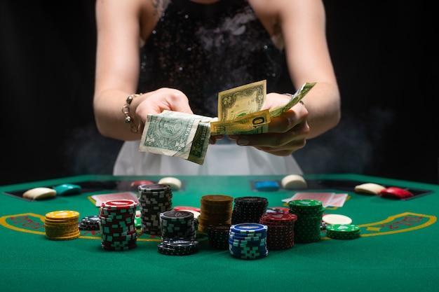 Девушка играет в покер и собирает свой выигрыш Premium Фотографии