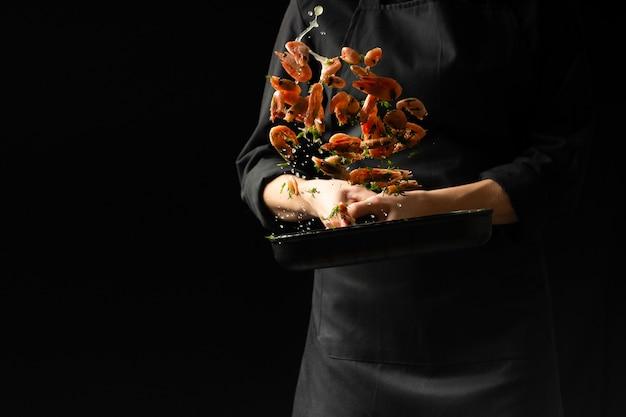 Профессиональный шеф-повар приготовил креветки. кулинарные морепродукты и еда на темном фоне. Premium Фотографии