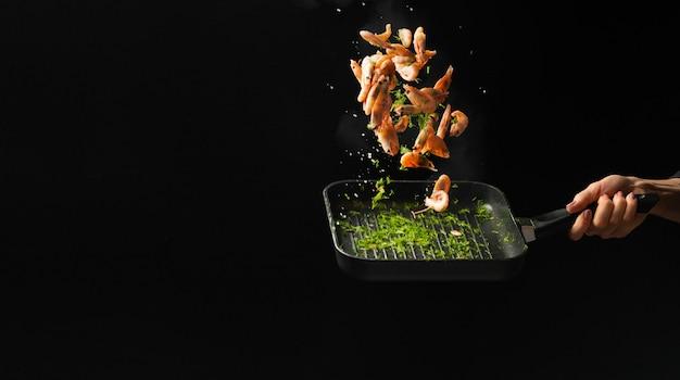 プロのシェフがエビを調理しました。料理用のシーフードと暗い背景の上に食べ物。 Premium写真