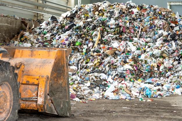 Куча пластиковых бутылок, бумаги и полиэтилена на заводе по переработке отходов перед сортировкой Premium Фотографии
